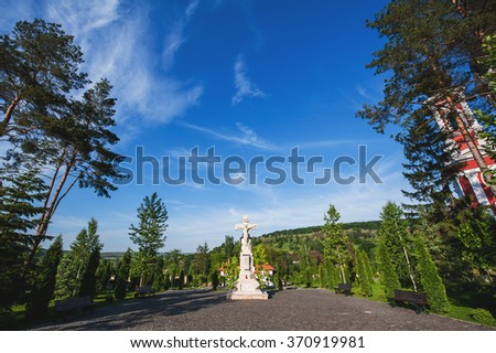 Crucifixion of Jesus statue on cobblestone place surrounded by green trees and beautiful forest in the perspective - stock photo