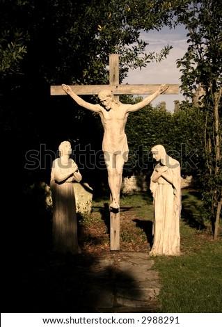 Crucifixion stone statue with praying mourners (Calvary) - stock photo