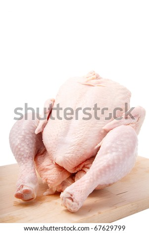 crude chicken on chopping board. It is isolated.