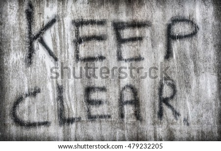 "Crude hand painted ""Keep Clear"" sign on faded wooden board."