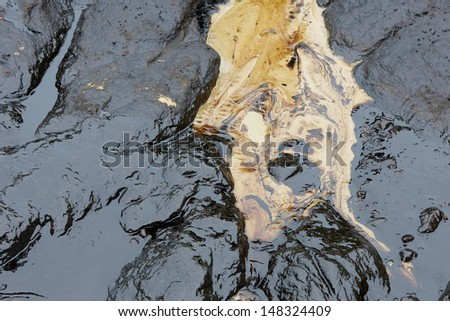 crude oil spill on the stone at the beach - stock photo