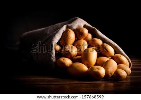 crude potato in linen bag on wooden table - stock photo