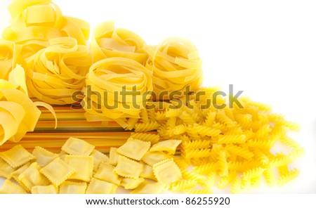 Crude yellow macaroni in bulk on a table - stock photo