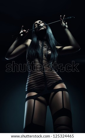 cruel woman with riding crop - stock photo