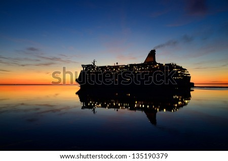 cruise ferry ship with it's reflection at the colorful sunset - stock photo