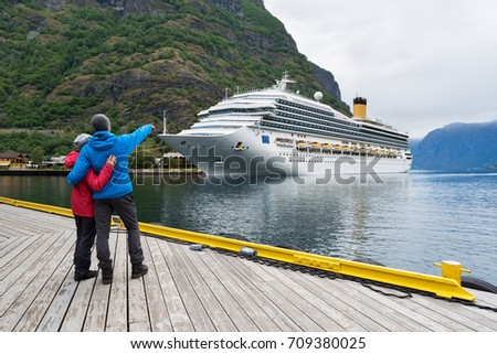 Cruise liner. Aurlandsfjord near the village of Flam, Norway. Young couple of travelers on the shore of the fjord