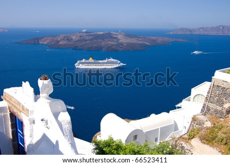 cruise liner motoring into the caldera below the cliffs of the capital city of fira on the greek island of santorini - stock photo
