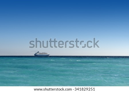 cruise liner sailing away on turquoise water and blue sky backround