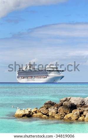 Cruise ship anchored in tropical waters with rocks in foreground - stock photo
