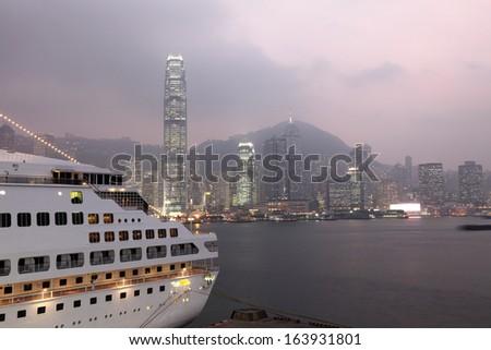 Cruise ship and skyline of Hong Kong at dusk - stock photo