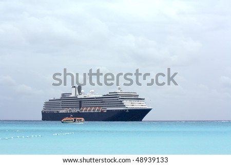 Cruise ship and tender on a light blue sea at Half Moon Cay in the Bahamas under cloudy skies - stock photo