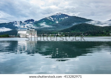 Cruise ship at a port in Juneau, Alaska with snow capped mountain and low lying fog in the background - stock photo