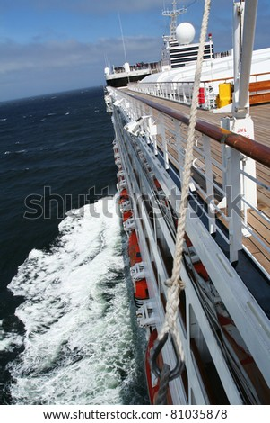 Cruise ship at high speeds on the open sea headed for a beautiful travel destination. - stock photo