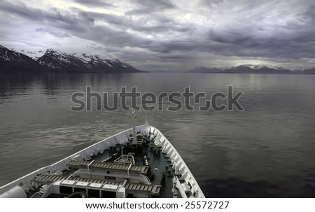 Cruise ship at Iceland with calm waters and snow capped mountains in background. - stock photo