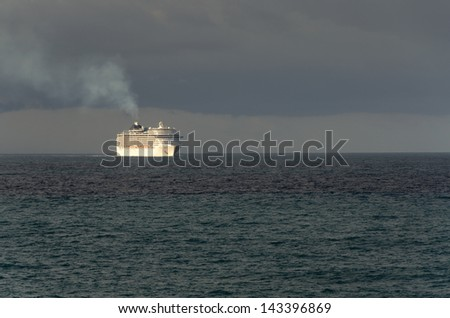 cruise ship at sunrise lit in the middle