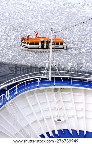 Cruise Ship bow passing icy snow arctic waters near Spitsbergen, Svalbard, Norway with lifeboat on water (Santa Claus on top view). - stock photo