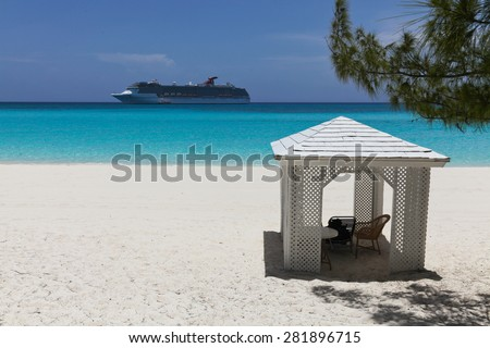 cruise ship close to a beach with a small relaxation building - stock photo