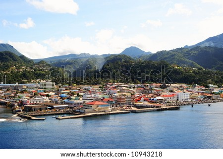Cruise ship coming into a caribbean city Roseau on the island of Dominica - stock photo