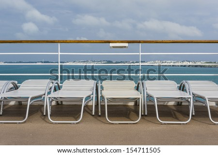 Cruise ship deck lounge chairs lined up in a row with a beautiful tropical background - stock photo