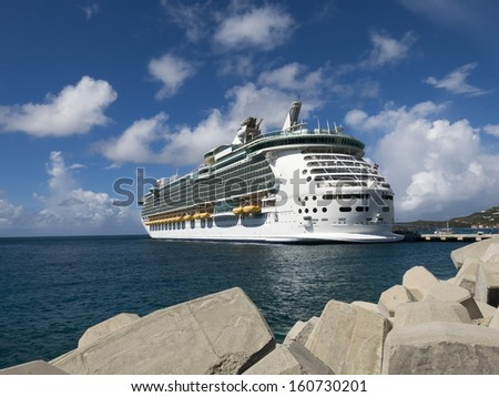 Cruise Ship Docked in Front of a Wall of Rocks with Blue Sky - stock photo