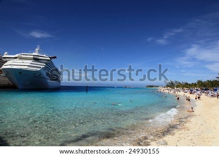 Cruise ship docked on tropical island beach resort - stock photo