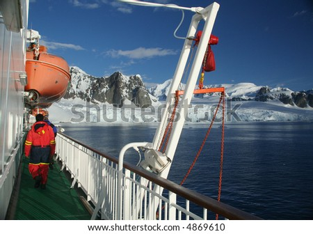 Cruise ship, icebreaker, with lifeboat, in calm seas, blue sky, with mountains & glaciers, 		Lemaire Channel,	Antarctica