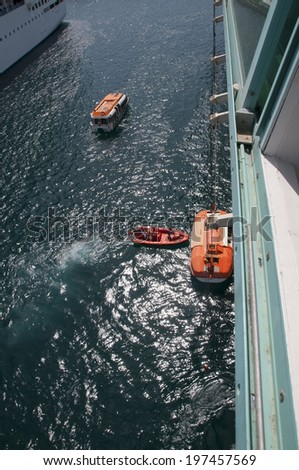 Cruise ship launching lifeboats during training drill - stock photo