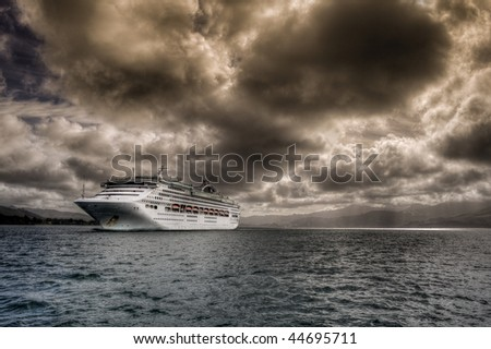 Cruise ship leaving Otago Harbour under stormy sky - stock photo