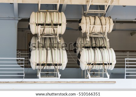 Cruise ship lifeboat blowup raft containers attached to a quick release rack