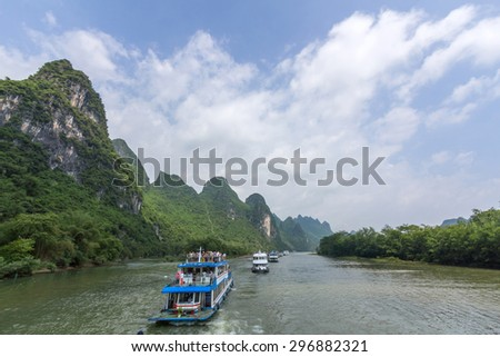 Cruise ship packed with tourists travels the magnificent scenic route along the Li river from Guilin to Yangshou. - stock photo