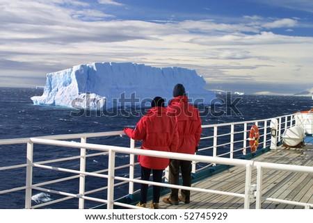 Cruise ship passengers looking at a beautiful iceberg at Antarctica - stock photo