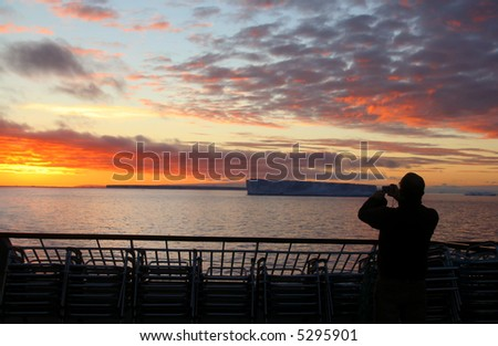 Cruise ship passengers taking pictures of sunset with tabular iceberg, Bransfield Strait,Antarctica - stock photo