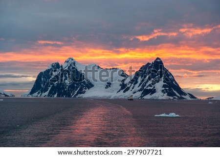 Cruise ship sailing through Lemaire Channel during stunning sunset, Antarctica - stock photo