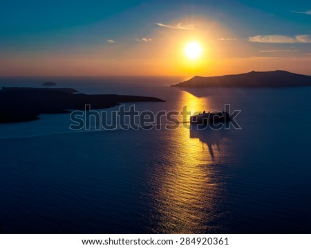 Cruise ship silhouette in sunset light with a few islands on background - stock photo