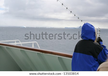 Cruise ship tourist in blue parka, taking pictures from the bow,Erreras Channel, Antarctica - stock photo