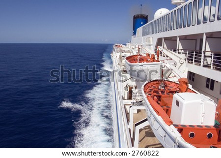 Cruise ship underway on the smooth ocean, showing lifeboats. - stock photo