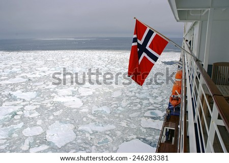 Cruise Ship with norwegian flag passing icy snow arctic waters near Spitsbergen, Svalbard, Norway - stock photo