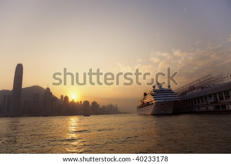 Cruise Ship with Skyline of Hong Kong at Sunset - stock photo