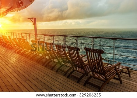Cruise Ship Wooden Deck Chairs. Cruise Ship Main Deck at Sunset. - stock photo