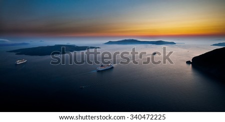Cruise ships sailing across aegean sea among scenic seascape under a clear summer sky during a vibrant sunset; at Cyclades islands, Greece. - stock photo