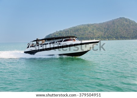 Cruise speed boat with tourists in the Andaman Sea, seacoast Thailand.