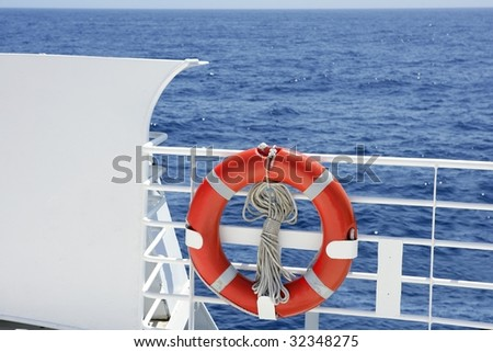 Cruise white boat handrail detail in blue sea and round orange buoy - stock photo