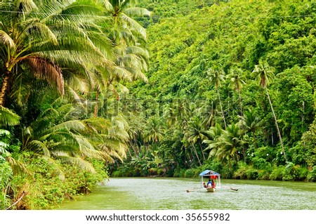 Cruising boat on Rainforest River - stock photo