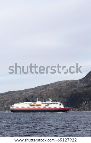 Cruising passenger ship in the Norwegian fjorda near Hammerfest - stock photo