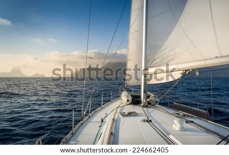 Cruising sailiing yacht with hoisted sails going to rock island. Evening warm light