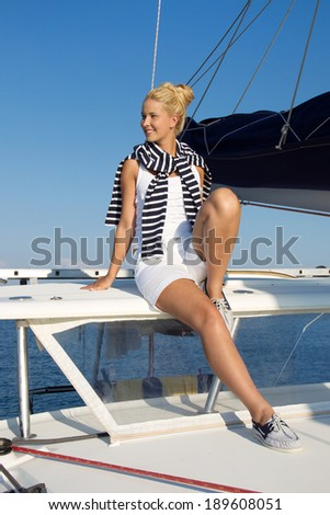 Cruising: Sailing woman on a luxury sail boat in summer.