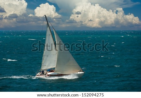 Cruising yacht sailing in racing of regatta. Nautical landscape with white sailboat on cloudy sky. Sea leisure - maritime romantic trip on the yacht. - stock photo