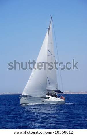 Cruising yachts in mediterranean sea on blue sky background - stock photo