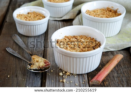 Crumble cake with rhubarb in a baking dish on a wooden background