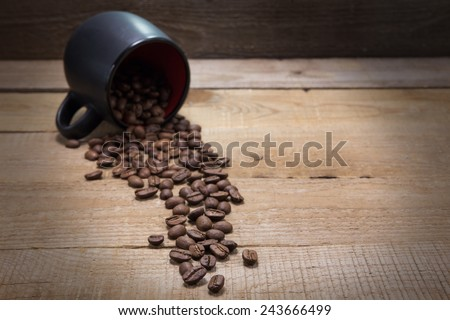crumble coffee beans and black circle on the wooden table - stock photo